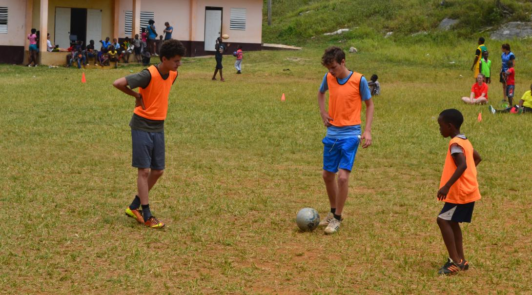 Volunteers warming up for soccer with a ball by practicing their passes in a triangle